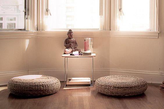 Una habitación con dos cojines y un pequeño mueble con figuras especiales pueden hacer un buen salón de meditación.